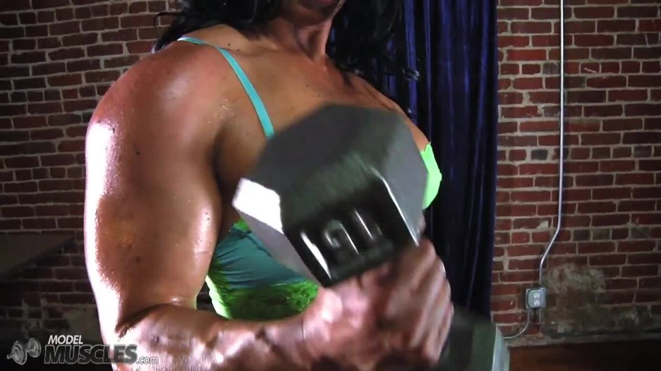 Tina Rock in green lingerie flexing her biceps